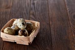 Quail eggs in a box on a rustic wooden background, top view, selective focus. Spotted quail eggs arranged in a box on a rustic wooden background, top view Stock Images