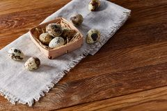 Quail eggs in a box on a rustic wooden background, top view, selective focus. Spotted quail eggs arranged on hay in a box on a rustic wooden background, top Royalty Free Stock Images
