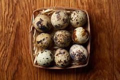 Quail eggs in a box on a rustic wooden background, top view, selective focus. Spotted quail eggs arranged in rows in a box on a rustic wooden background, top Stock Photo