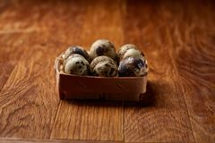 Quail eggs in a box on a rustic wooden background, top view, selective focus. Spotted quail eggs arranged in rows in a box on a rustic wooden background, top Royalty Free Stock Photos