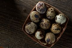 Quail eggs in a box on a vintage wooden background, top view, selective focus. Spotted quail eggs arranged in rows in a box on a vintage wooden background, top Stock Photography