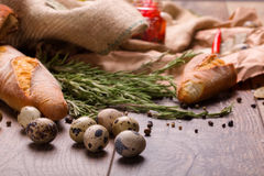 Quail eggs, bread, rosemary and spices on a wooden table background. Nutritious and protein ingredients for a dinner. Royalty Free Stock Photos