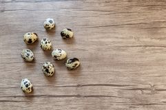 Quail eggs on brown wooden background. Flat lay, top view. Easter concept. Simple Easter flat lay still life with quail eggs on brown wooden background royalty free stock photo