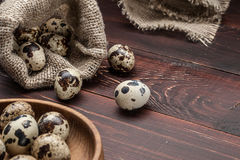 Quail eggs in burlap sack over old wooden background Royalty Free Stock Photography
