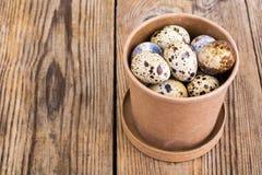 Quail eggs in cardboard box on wooden table. Studio Photon Stock Photo