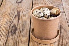 Quail eggs in cardboard box on wooden table. Studio Photon Royalty Free Stock Photos