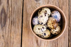 Quail eggs in cardboard box on wooden table. Studio Photon Royalty Free Stock Photography