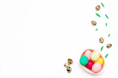 Quail eggs and chicken colorful eggs in a pink basket on white background. Stock Photos