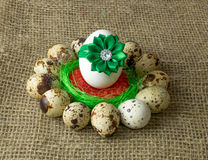 Quail eggs and chicken egg with green bow are in a circle around the plastic blue bowl of red salt on a wooden table Stock Photos