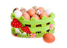 Quail eggs and chicken in green decorative basket Stock Photos