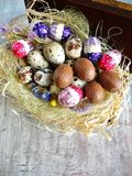 Quail eggs and chocolate eggs on the table Royalty Free Stock Image