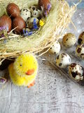 Quail eggs and chocolate eggs on the table Royalty Free Stock Photos