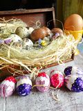 Quail eggs and chocolate eggs on the table Royalty Free Stock Images
