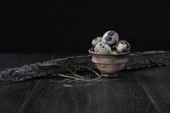 Quail eggs in clay pot on dark background. Eco products Royalty Free Stock Photos