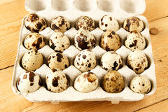 Quail eggs in a container. On a wooden background Stock Photography