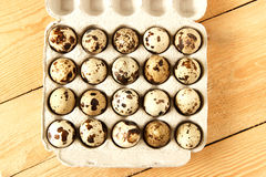 Quail eggs in a container. On a wooden background Stock Photo