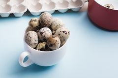 Quail eggs in cup and cardboard packaging on blue background..Vegetarian organic food. Eco products cocept. Quail eggs in cup, red saucepan and cardboard royalty free stock photography