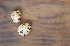 Quail eggs on a dark brown wooden surface, top view, empty place. For text, recipe Stock Photos