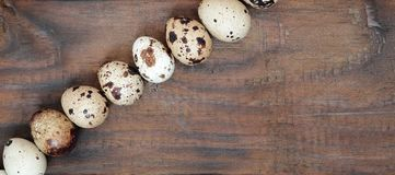 Quail eggs on a dark brown wooden surface, top view, empty place. For text, recipe Royalty Free Stock Photography