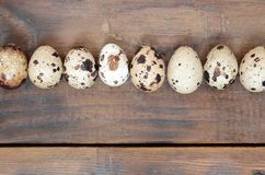 Quail eggs on a dark brown wooden surface, top view, empty place. For text, recipe Royalty Free Stock Photo