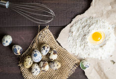 Quail eggs, flour, whisk on wooden background Stock Photography