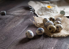 Quail eggs, flour, whisk on wooden background Stock Images
