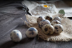 Quail eggs, flour, whisk on wooden background Royalty Free Stock Photos