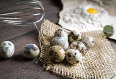 Quail eggs, flour, whisk on wooden background Stock Photos