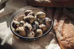 Quail eggs and fresh white bread, a loaf on the tablecloth. Quail eggs on a plate Stock Image