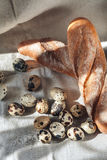 Quail eggs and fresh white bread, a loaf on the tablecloth. Quail eggs on a plate Stock Photo
