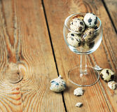Quail eggs in a glass on a wooden table Stock Photos