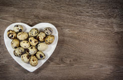 Quail eggs in a heart shaped plate. On wood background stock image