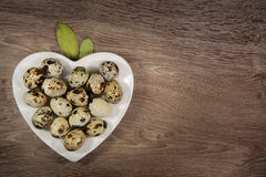 Quail eggs in a heart shaped plate on wood. Quail eggs in a heart shaped plate with a bay leaf on wood background royalty free stock image