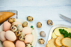 Quail eggs and hen egg with bread and butter. On the white wooden table. Selective focus Stock Image