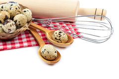 Quail eggs and kitchen utensils on white background. Royalty Free Stock Photo