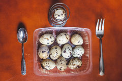 Quail eggs lie in transparent box. Near fork, spoon Royalty Free Stock Image