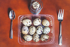 Quail eggs lie in transparent box. Near fork, spoon Royalty Free Stock Images