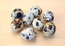 Quail eggs lie on a wooden table Royalty Free Stock Photos