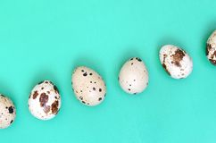 Quail eggs on a light green surface, top view, empty place for t. Ext, recipe stock photo