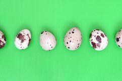 Quail eggs on a light green surface, top view, empty place for t royalty free stock photography