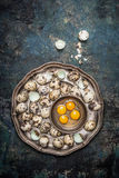 Quail eggs in metal plate on rustic background Stock Photo