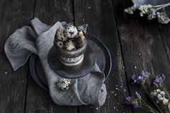 Quail eggs in metal rustic bowl on wooden country table on linen. Quail  eggs in metal rustic bowl and black ceramic plates with white small flowers and splited Royalty Free Stock Photos