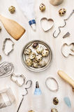 Quail eggs in metallic bowl and easter baking tools on white wooden background Royalty Free Stock Photos
