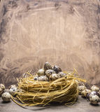 Quail eggs  nest border ,place for text on wooden rustic background top view close up Stock Photo