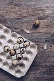 Quail eggs in a package on a wooden table with feathers. View from above. Quail eggs in a package on a wooden table with feathers. View from above Royalty Free Stock Photography