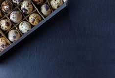 Quail eggs in a paper box. Top view of quail eggs in paper box on a stone texture Royalty Free Stock Image