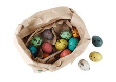 Quail eggs in a paper package. Colored quail eggs in a package of brown paper on white background. Isolated with clipping path. Top view Stock Photography