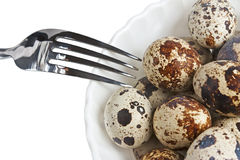 Quail eggs on a plate and fork. Isolated Royalty Free Stock Image