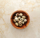 Quail eggs in a plate on a marble background. Quail eggs in a wooden bowl on a marble background, top view Royalty Free Stock Image