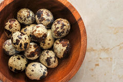 Quail eggs in a plate on a marble background. Quail eggs in a wooden bowl on a marble background, top view Stock Photography